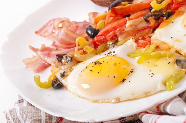 Café da manhã - ovos fritos com bacon, tomate, azeitona e fatias de queijo