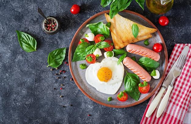Café da manhã - ovos fritos em forma de coração, salsicha, torradas e salada caprese de tomate, manjericão e mussarela. comida caseira e saborosa. vista do topo. configuração plana