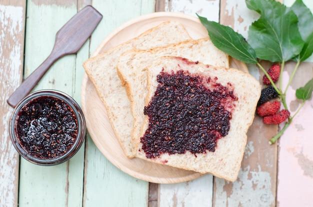 Café da manhã: pão caseiro com geléia de amora na mesa de madeira