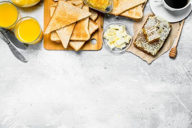 Café da manhã. pão torrado, café com suco de laranja e geléia em mesa rústica