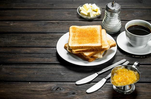 Café da manhã. pão torrado com manteiga e café aromático. em uma madeira.