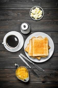 Café da manhã. pão torrado com manteiga e café aromático na mesa rústica.