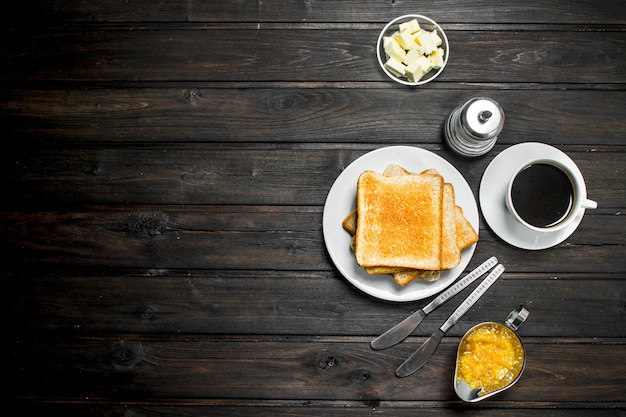 Café da manhã. pão torrado com manteiga e café aromático. sobre uma superfície de madeira.