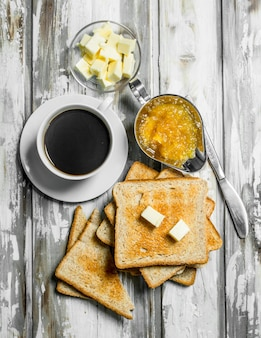 Café da manhã. pão torrado com manteiga e café quente. na superfície de madeira rústica.