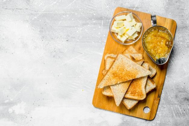 Café da manhã. pão torrado com manteiga e geléia em uma placa de madeira. sobre uma mesa rústica.