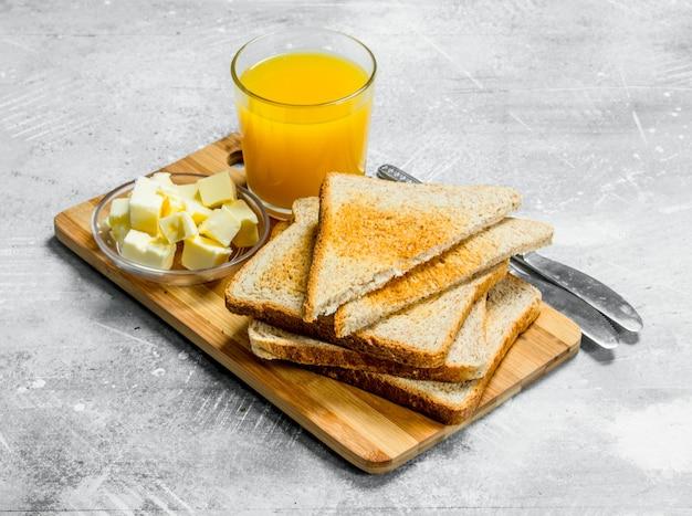 Café da manhã. pão torrado com manteiga e um copo de suco de laranja. em um rústico.