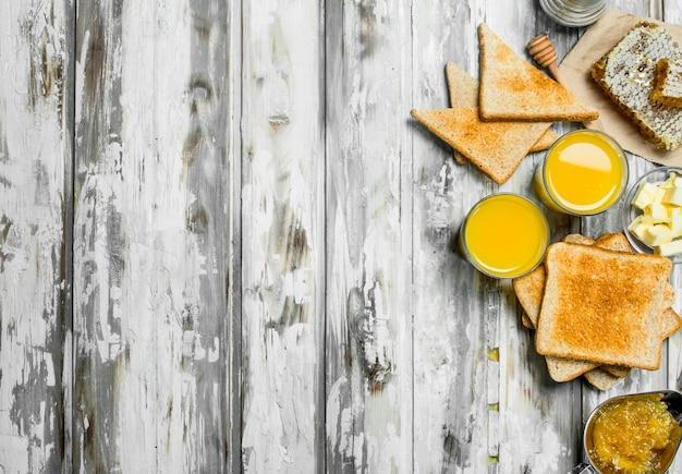 Café da manhã. pão torrado com manteiga, mel e sumo de laranja. em madeira rústica.