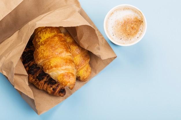 Café da manhã para ir - croissants e café com leite no espaço cinza. entrega de produtos. vista superior, espaço de cópia