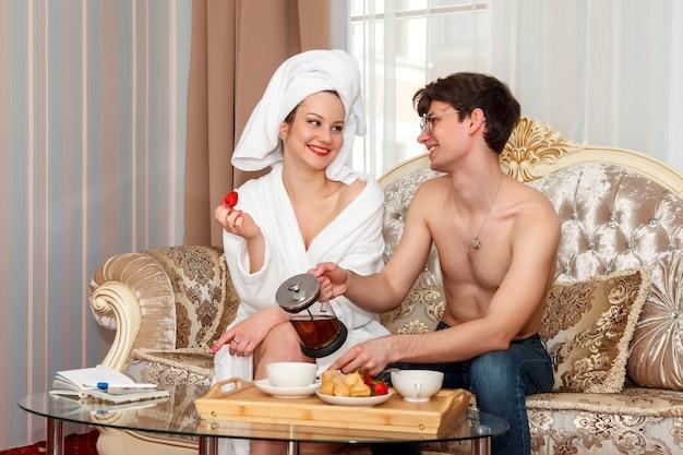 Café da manhã para recém-casados. lindo casal feliz em roupões, sorrindo um para o outro e bebendo chá enquanto toma o café da manhã no sofá. conceito de conforto do lar e bem-estar familiar. felicidade nos olhos