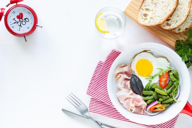 Café da manhã para seu amado no feriado: ovo em forma de coração, bacon, feijão verde em uma mesa branca. foco seletivo. vista de cima. copie o espaço