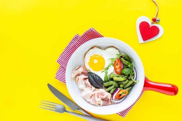 Café da manhã para sua amada no feriado: ovo em forma de coração, bacon, feijão verde sobre fundo amarelo. foco seletivo. vista de cima. copie o espaço