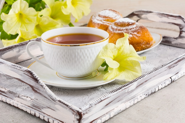 Café da manhã pastelaria dinamarquesa e xícara de chá na bandeja de servir vintage
