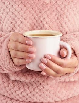 Café da manhã quente na manhã fria de outono, mãos segurando uma caneca com uma bebida, ambiente acolhedor