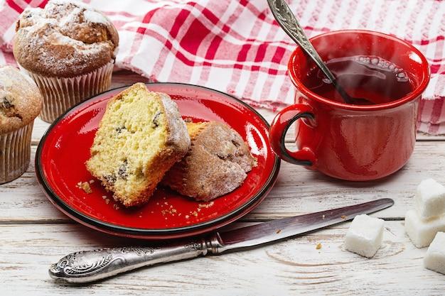 Café da manhã. queques frescos e chá quente em copo vermelho.