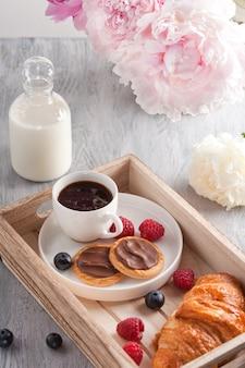 Café da manhã romântico com café, croissant, biscoitos de chocolate e frutas silvestres