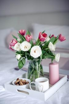 Café da manhã romântico na cama. buquê de flores. rosas e tulipas.