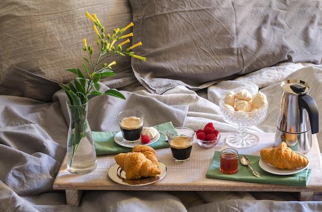 Café da manhã romântico para dois dentro de um quarto. cafeteira e copos de café, croissants, geléia, merengue de framboesa e flores na bandeja de madeira