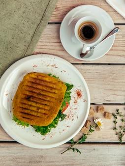 Café da manhã rústico com cappuccino e sanduíche na mesa de madeira com garfo e faca