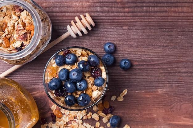 Café da manhã rústico com granola e mel no fundo de madeira, vista superior