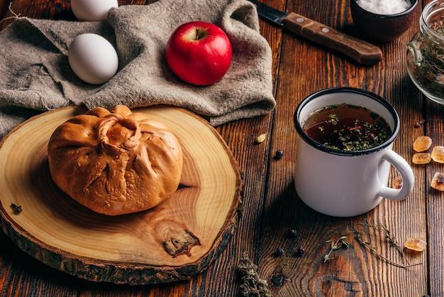 Café da manhã rústico com massa tradicional tártara elesh, chá de ervas em caneca de metal