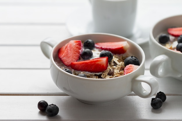 Café da manhã saboroso com farinha de aveia, iogurte, morango, mirtilo, mel e leite em fundo de madeira branco com espaço de cópia. fechar-se.