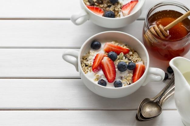 Café da manhã saboroso com farinha de aveia, iogurte, morango, mirtilo, mel e leite em fundo de madeira branco com espaço de cópia. vista do topo.