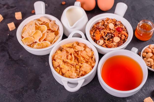 Café da manhã saboroso e útil com flocos, leite, nozes e frutas secas