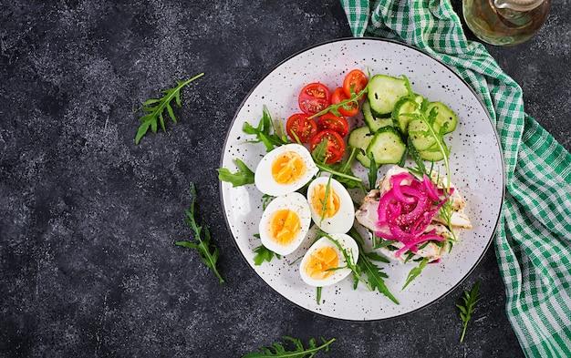 Café da manhã. salada de ovos cozidos com verduras, pepino, tomate e sanduíche com ricota, filé de frango frito e cebola roxa. almoço keto / paleo. vista superior, sobrecarga