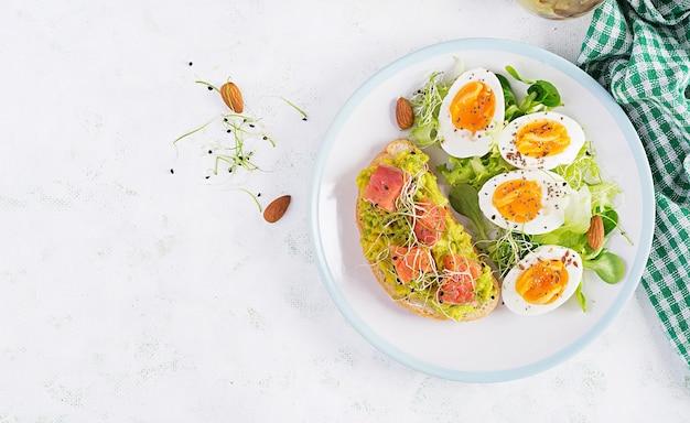 Café da manhã. sanduíche aberto saudável na torrada com abacate e salmão, ovos cozidos, ervas, sementes de chia na chapa branca com espaço de cópia. proteína alimentar saudável. vista superior, sobrecarga