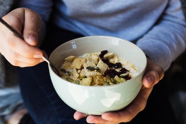 Café da manhã saudável. a garota come granola fresca, muesli com nozes de frutas de leite. vista de cima.