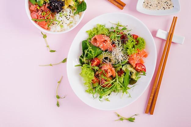 Café da manhã saudável. bacia de buda com arroz, manga, abacate e salmão e sanduíche de salmão com abacate