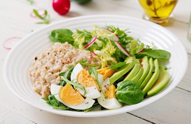 Café da manhã saudável. cardápio dietético. mingau de aveia e salada de abacate e ovos.