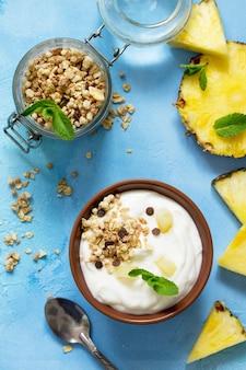Café da manhã saudável caseiro em uma tigela com granola caseira assada, abacaxi fresco e iogurte