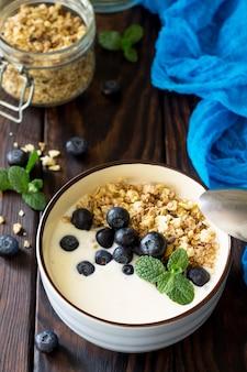 Café da manhã saudável caseiro em uma tigela com mirtilos frescos de granola caseira assada