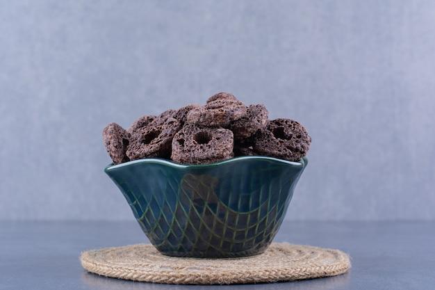 Café da manhã saudável com anéis de milho de chocolate em um prato sobre uma pedra.