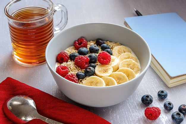 Café da manhã saudável com aveia em uma tigela, rodelas de banana, framboesa, mirtilo, uma xícara de chá e um caderno com uma caneta na mesa cinza claro Foto Premium