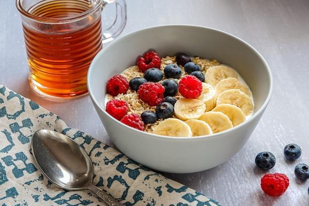 Café da manhã saudável com aveia em uma tigela, rodelas de banana, framboesa, mirtilo, uma xícara de chá e um caderno com uma caneta na mesa cinza claro