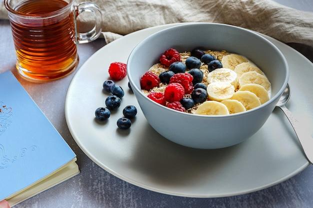 Café da manhã saudável com aveia em uma tigela, rodelas de banana, framboesa, mirtilo, uma xícara de chá e um caderno na mesa cinza claro