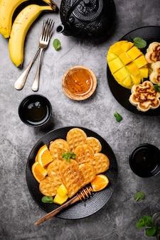 Café da manhã saudável com corações de waffles quentes frescos, flores de panquecas com mel de baga e frutas exóticas na superfície cinza, vista superior, plana leiga. conceito de comida