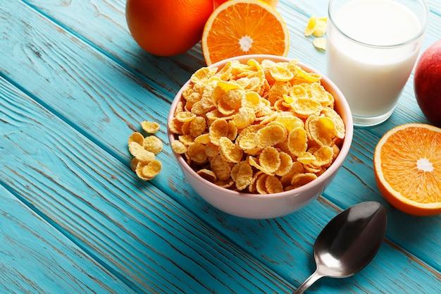 Café da manhã saudável com flocos de milho e frutas em um fundo azul de madeira. lugar para texto. vista do topo.