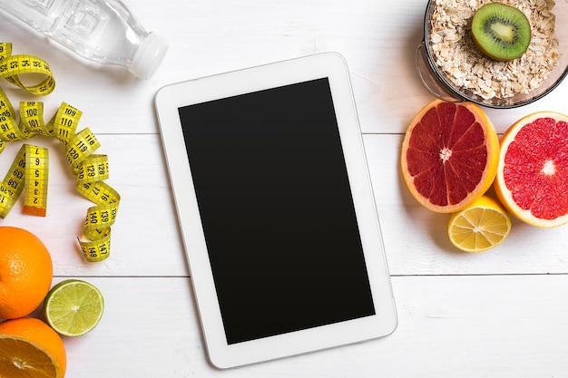 Café da manhã saudável com frutas frescas de aveia e garrafa de água com tablet na mesa de madeira rústica