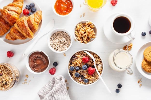 Café da manhã saudável com granola, amora, nozes, croissant, geléia, chocolate e café. vista do topo