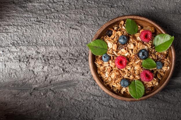 Café da manhã saudável com granola e frutas vermelhas em fundo escuro