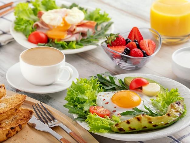Café da manhã saudável com ovos fritos, abacate, tomate, brindes e café e suco de laranja.