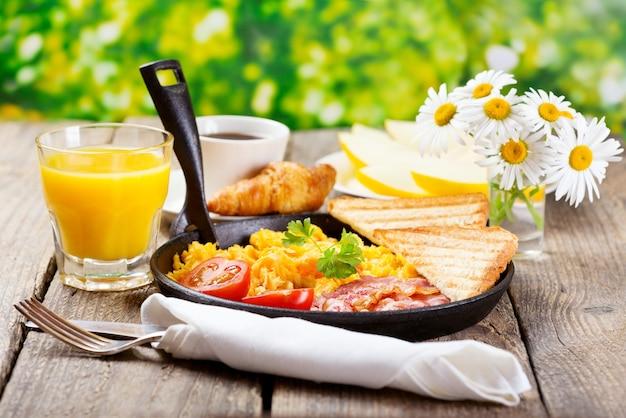 Café da manhã saudável com ovos mexidos, suco e frutas na mesa de madeira