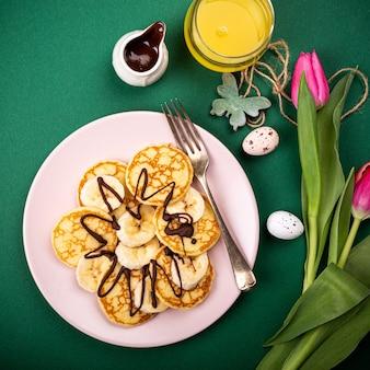 Café da manhã saudável com panquecas quentes frescas com bananas e chocolate na superfície verde, vista de cima