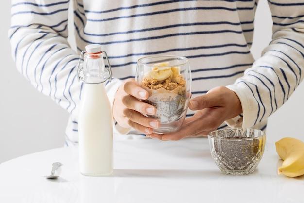Café da manhã saudável com sementes de iogurte, nozes, banana e chia. taça de fruta fresca.