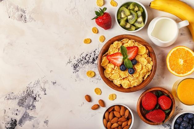 Café da manhã saudável com tigela de muesli, bagas e frutas, nozes, suco de laranja, leite