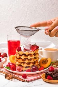 Café da manhã saudável com waffles belgas com morangos, damascos, cerejas, suco e uma xícara de café preto. mão de mulher borrifa pó de uma peneira em waffles