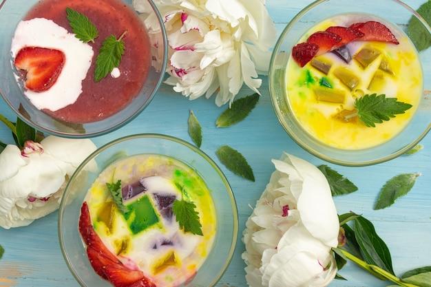 Café da manhã saudável de geleia de leite com frutas frescas em tigelas de vidro em uma mesa rústica azul